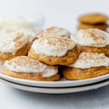 a stack of pumpkin cookies with cream cheese frosting on a white plate
