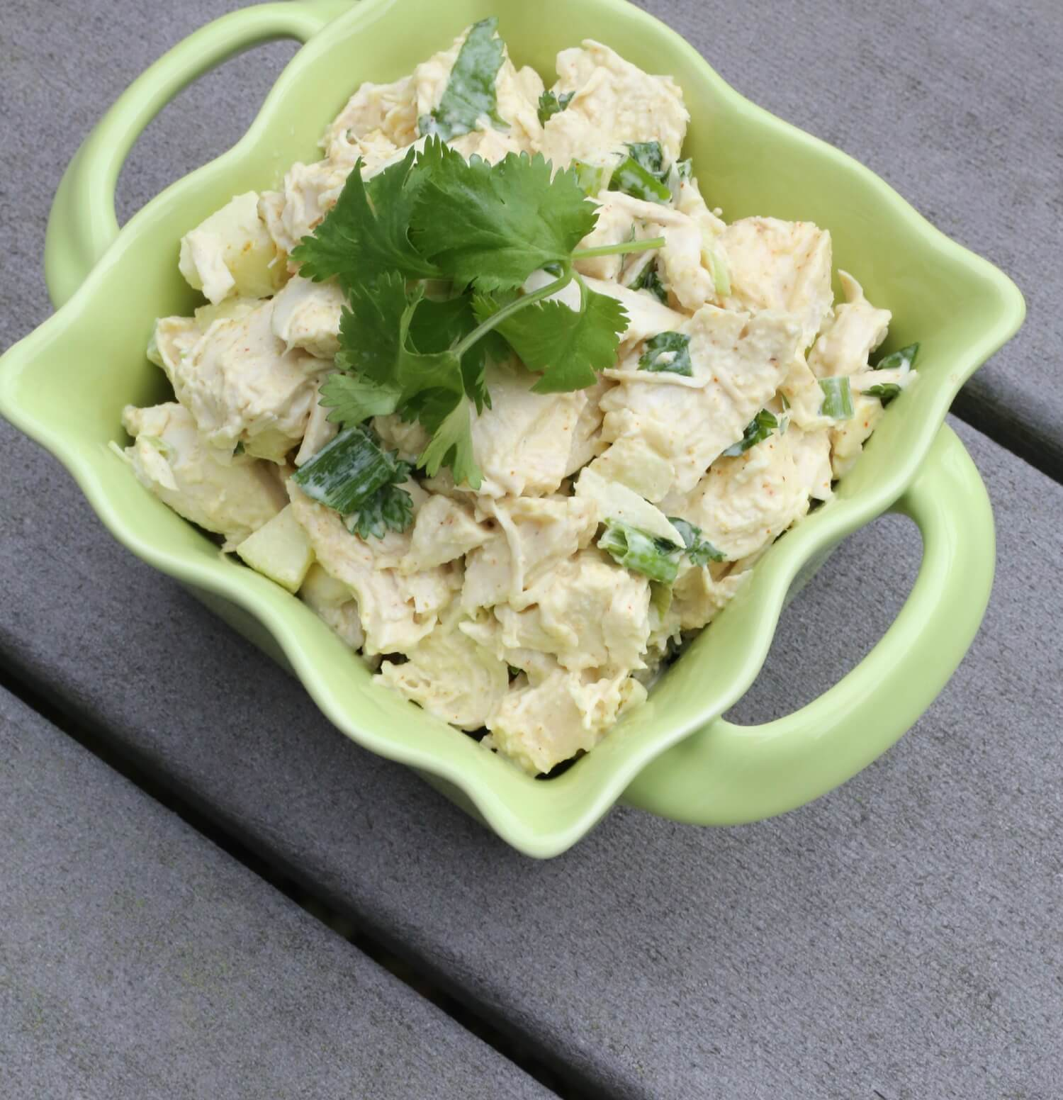 curry chicken salad in a bowl topped with scallions