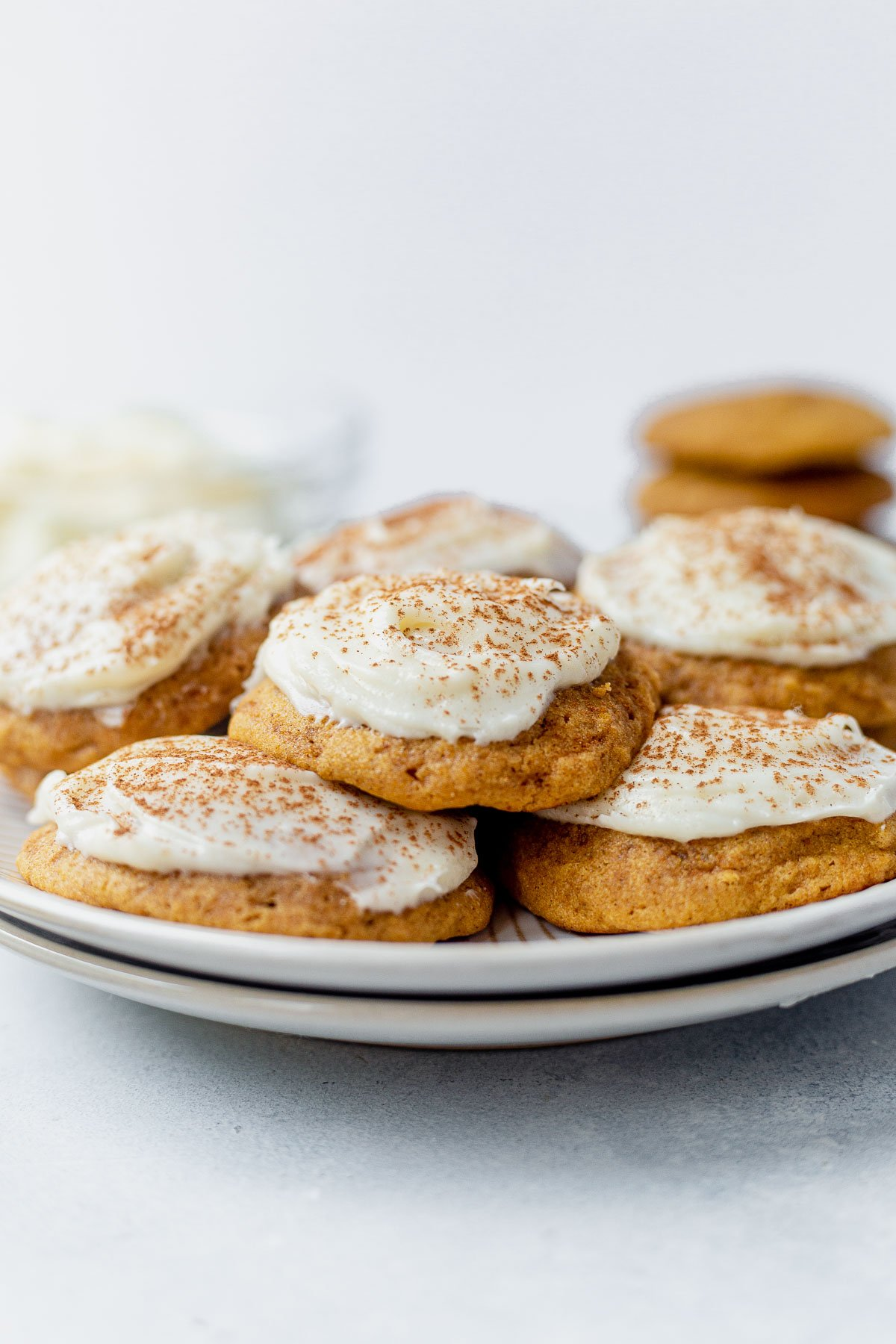 soft pumpkin cookies with cream cheese frosting on a white plate