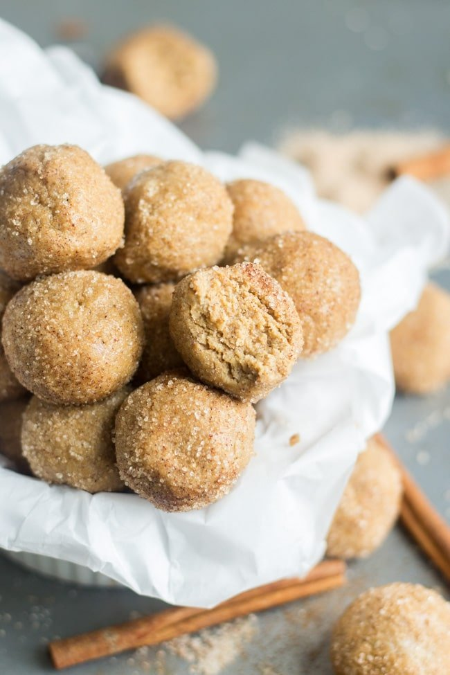 snickerdoodle protein balls on parchment paper with a bite taken out of one