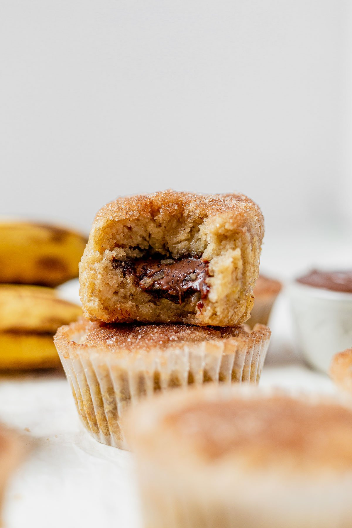 two banana nutella muffins stacked on top of each other and the top one has a bite taken out so you can see the gooey nutella inside