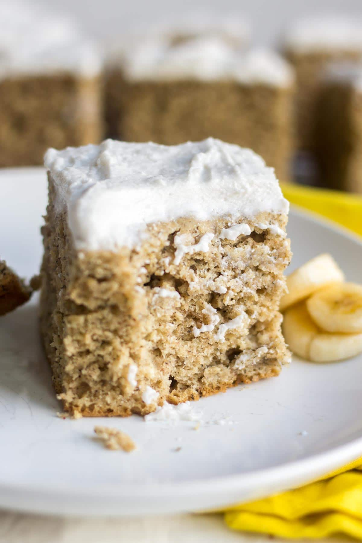 healthy banana cake recipe on a white plate with a bite taken out