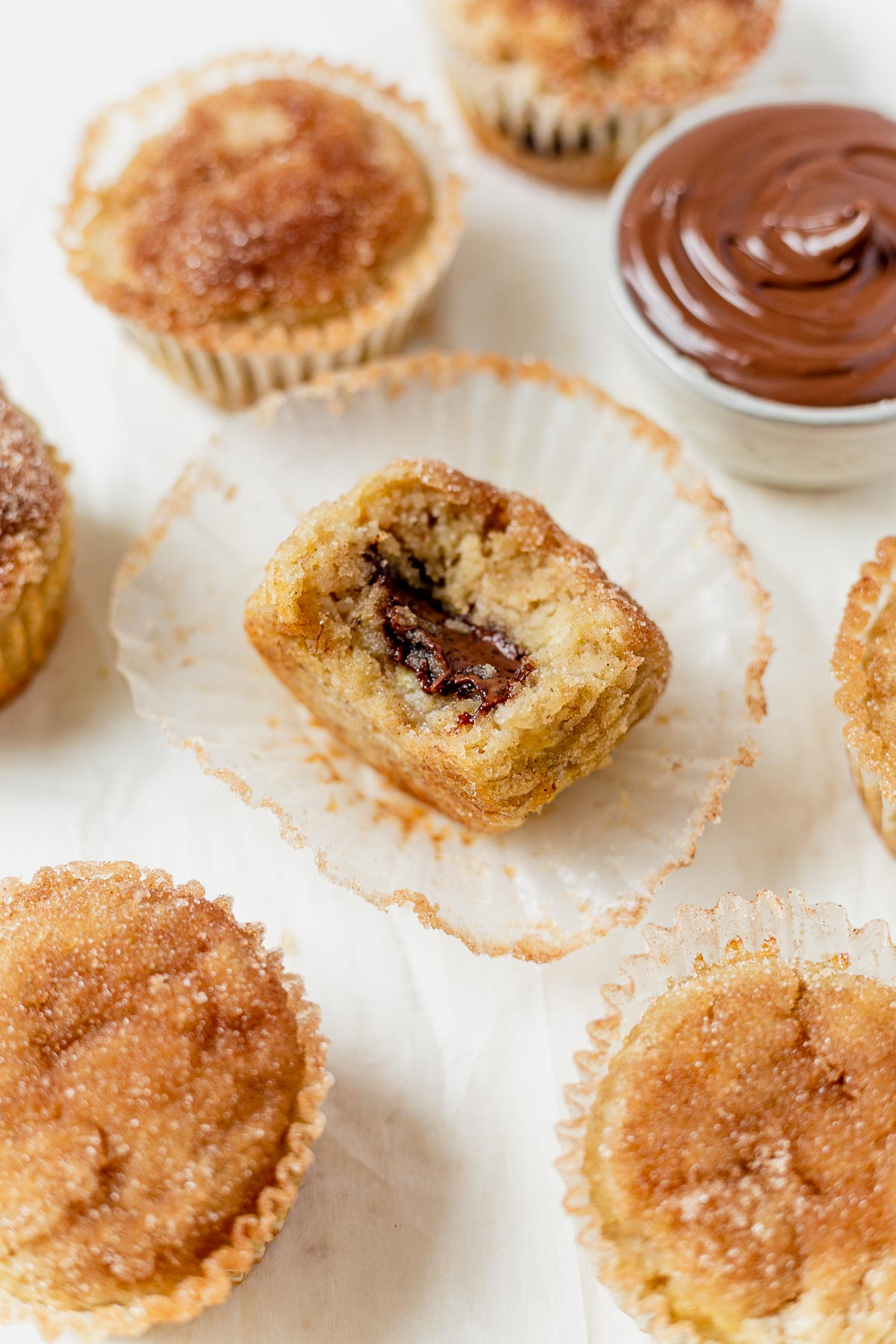 a banana nutella muffin with a bite taken out sitting inside a paper muffin liner with more muffins surrounding it