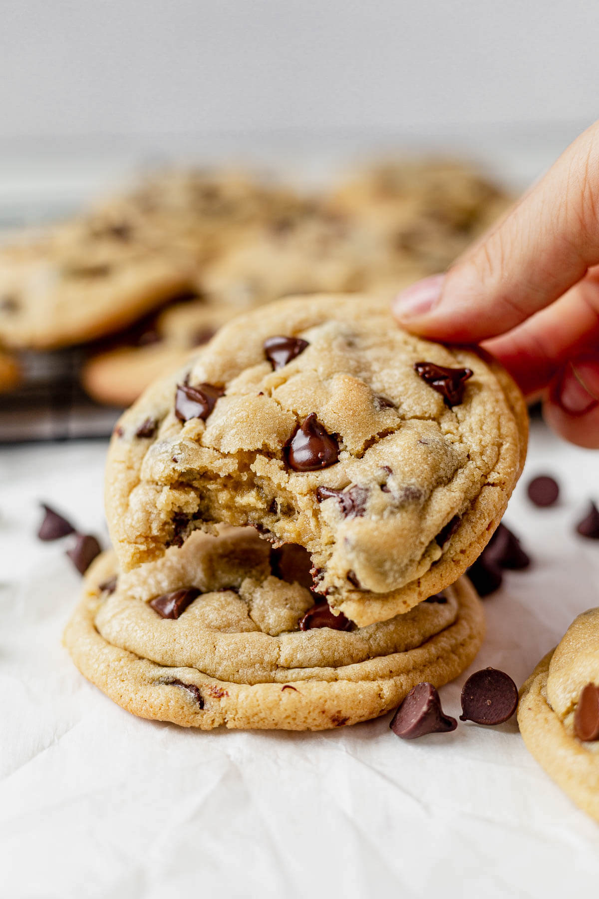 two chocolate chip pudding cookies stacked on top of each other with a bite taken out of the top one