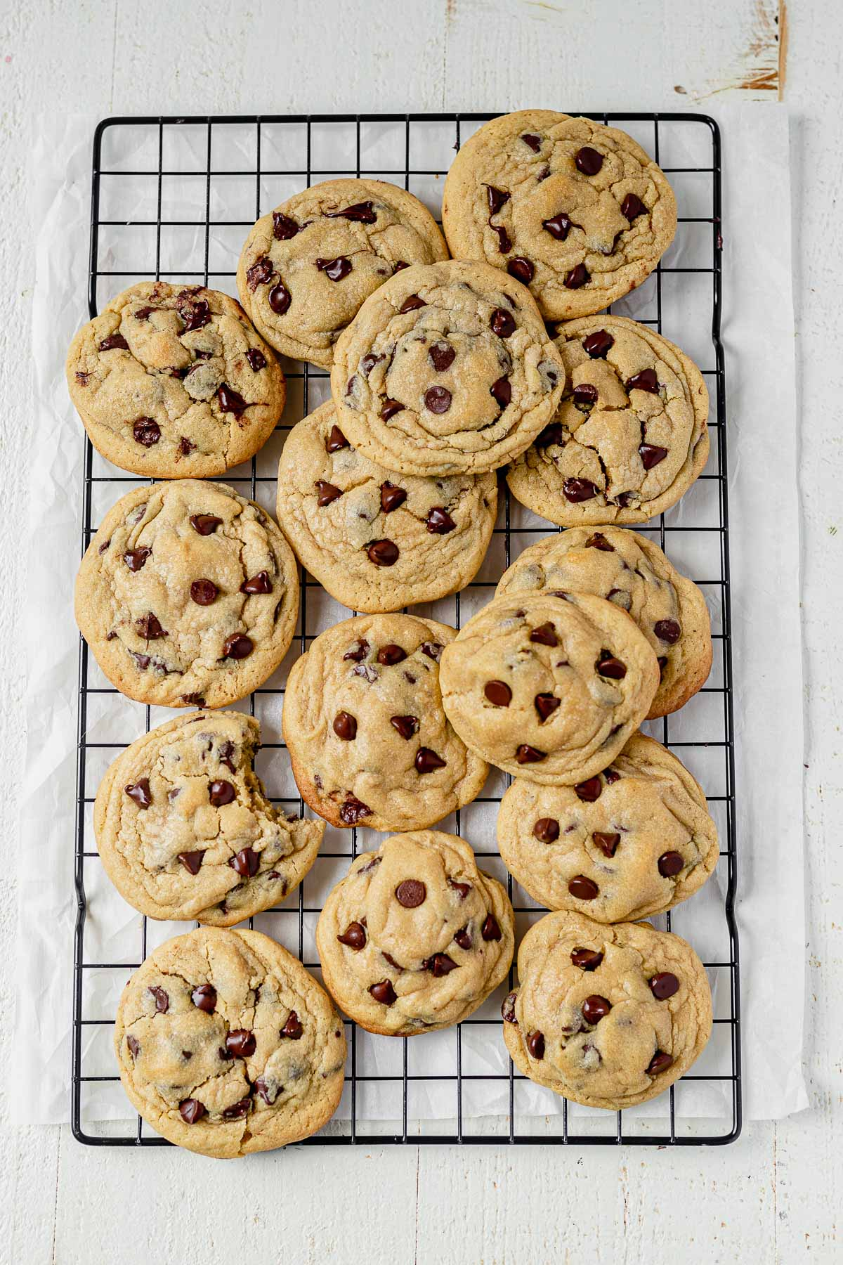 15 chocolate chip cookies made with vanilla pudding cooling on a black cooling rack