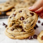 a gooey chocolate chip pudding cookie with a bite taken out sitting on top of another fresh baked cookie