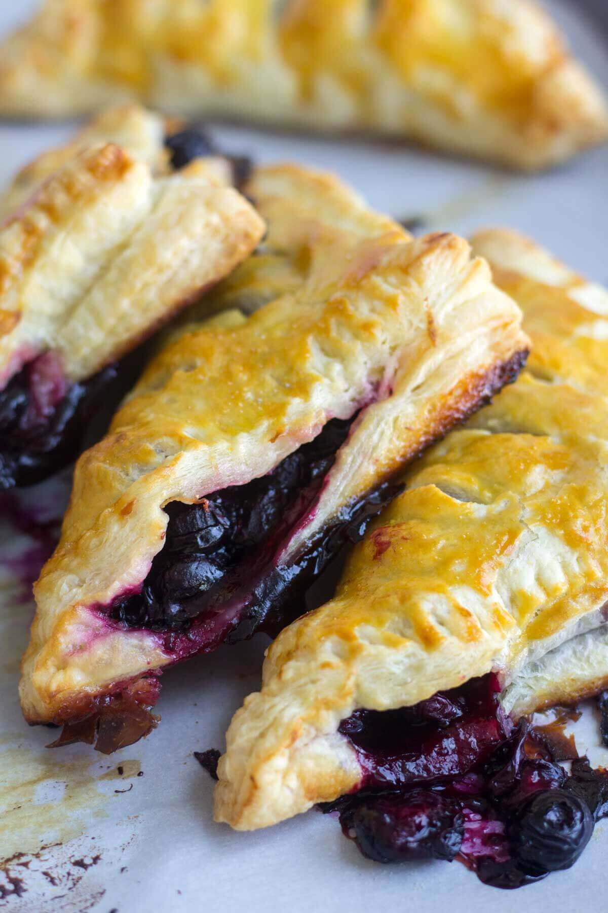 three blueberry turnovers stacked next to each other