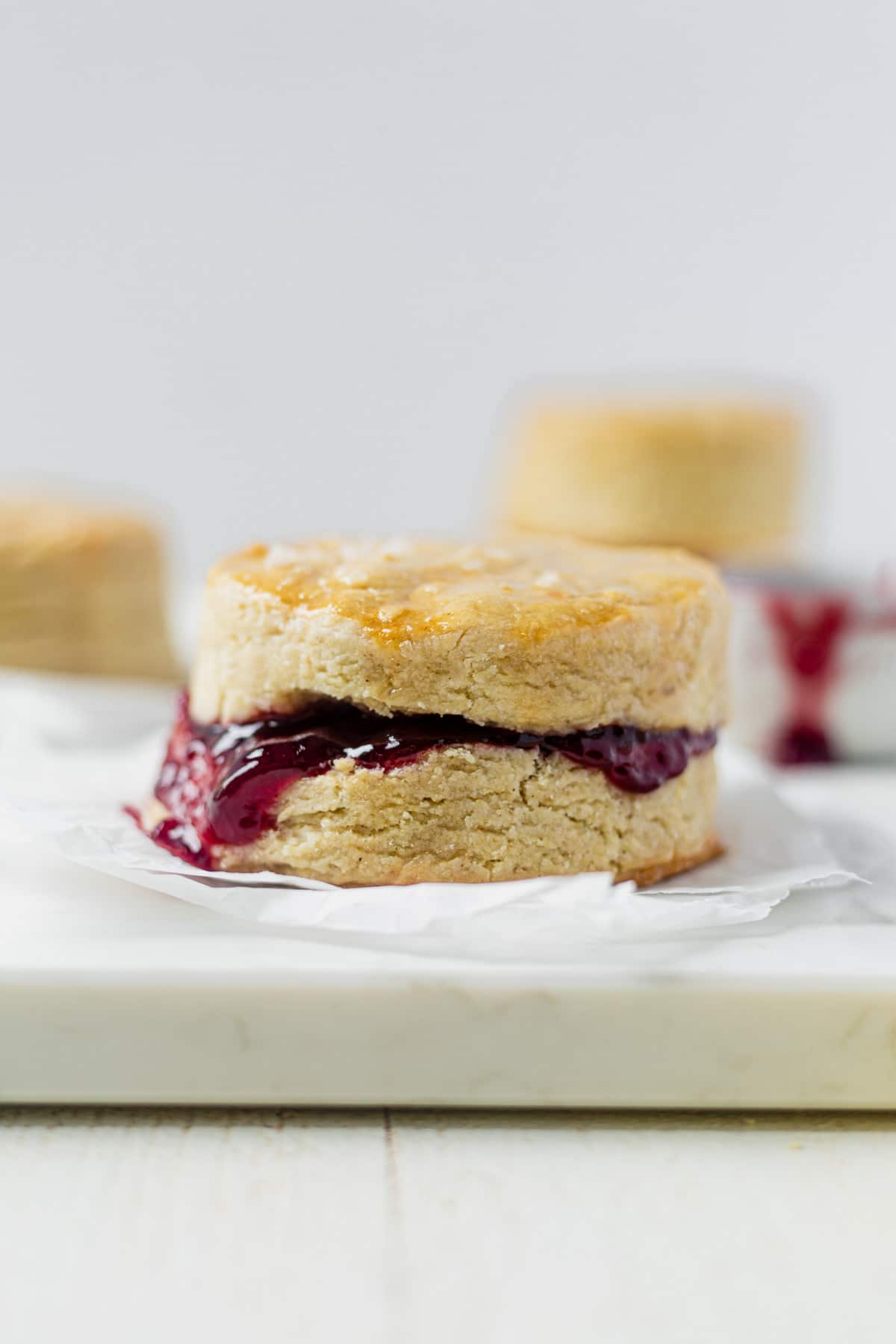 a flaky golden brown vegan biscuits filled with strawberry jam that's oozing out of the side