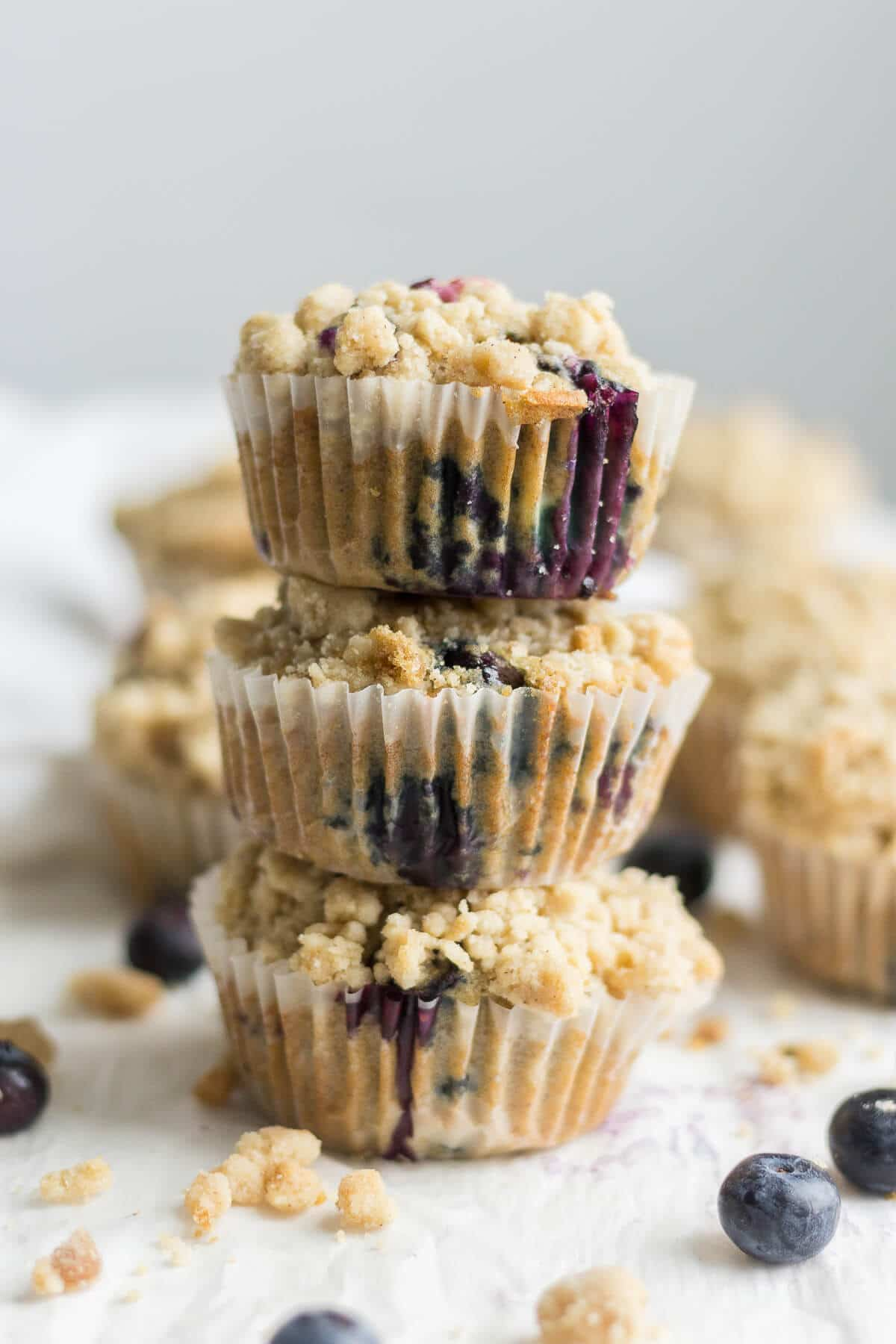 three blueberry crumb muffins stacked on top of each other