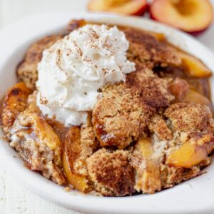 a large serving of gluten free peach cobbler in a white dish topped with whipped cream and cinnamon
