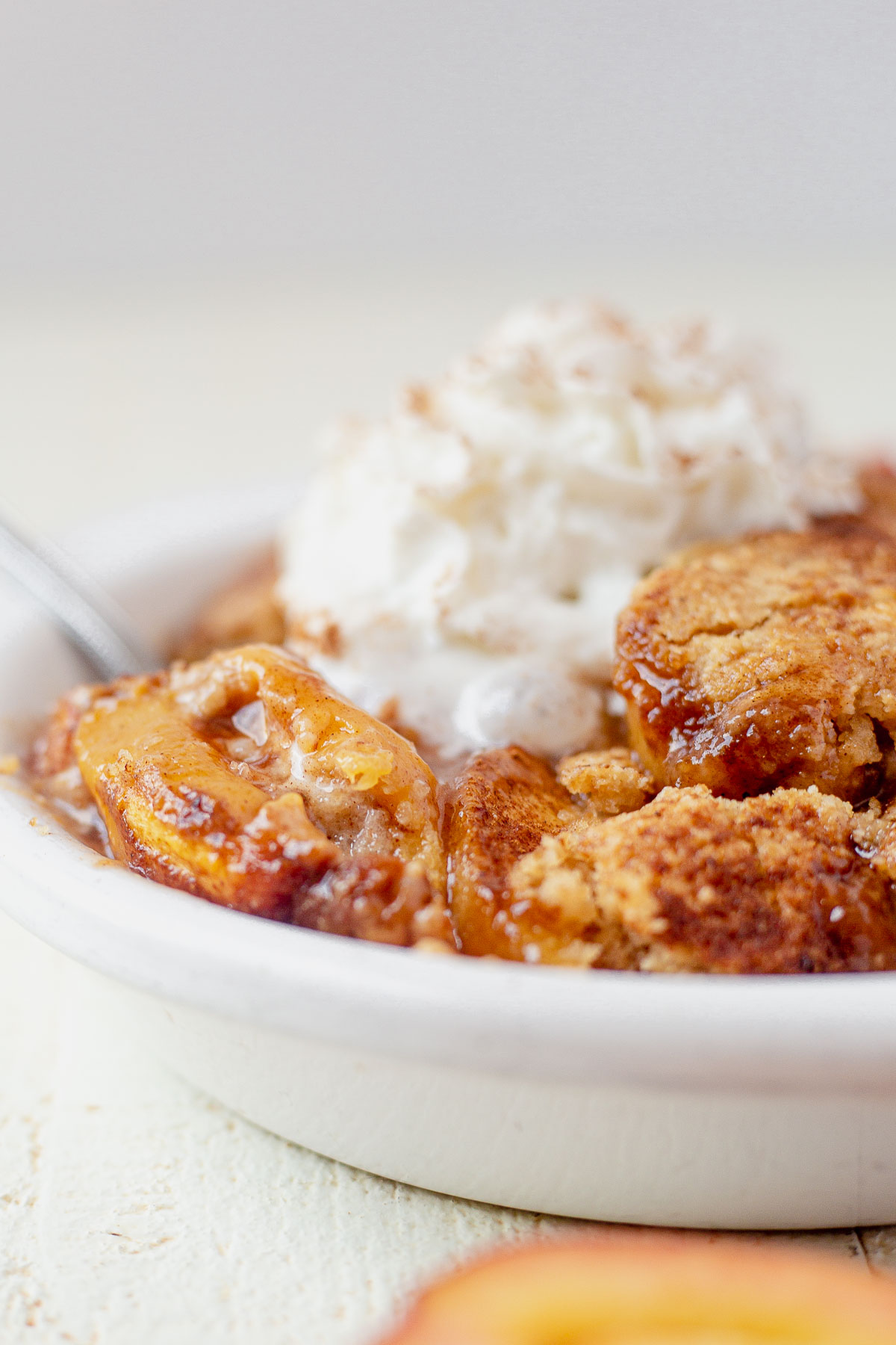 gooey peaches in a white serving dish with gluten free cobbler topping and whipped cream