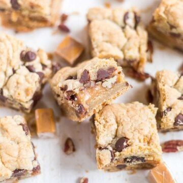 Thick and chewy turtle cookie bars! The base of this recipe is a chocolate chip cookie. You'll split the dough in half and add some caramel and pecans to the middle for an easy, chewy dessert!