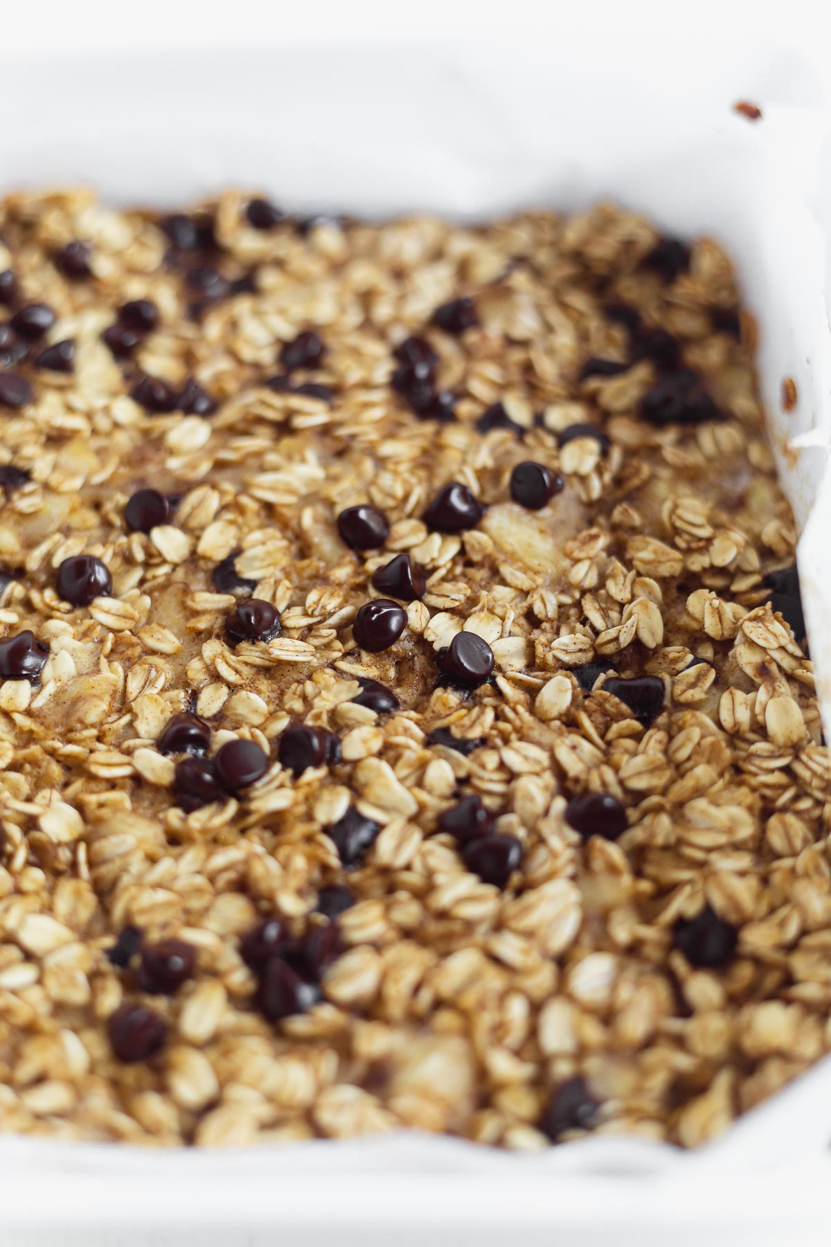 baked oatmeal with banana and chocolate chips in a white 8x8 inch baking dish