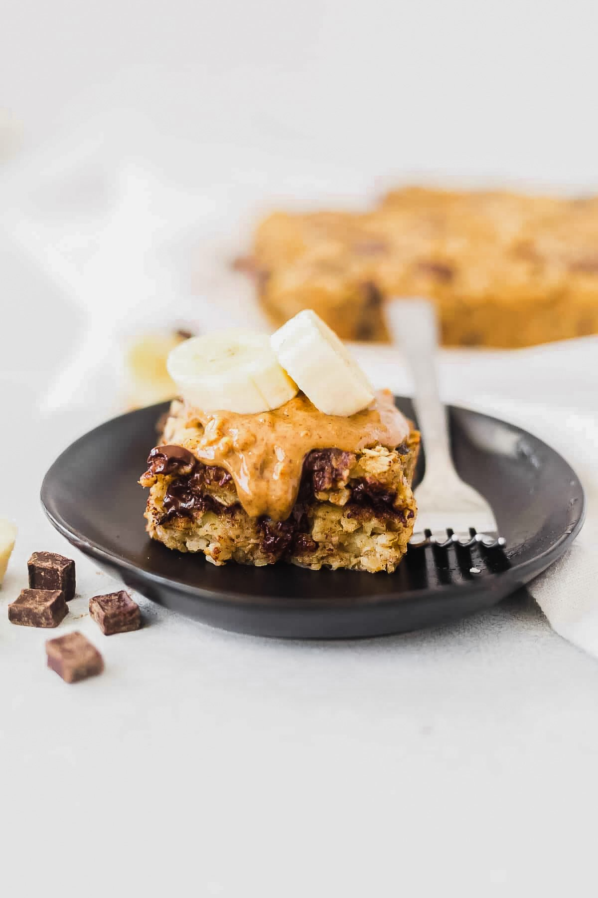 a slice of banana baked oatmeal on a black dessert dish topped with almond butter and banana and served with a fork