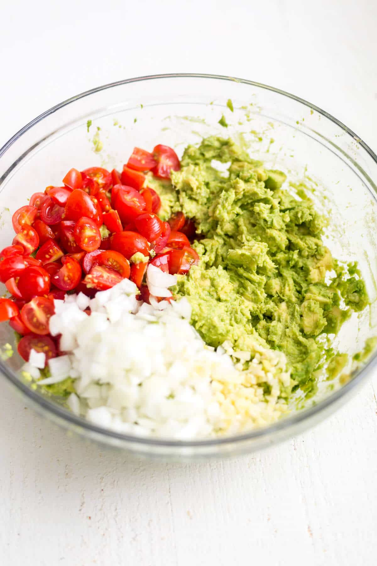 healthy guacamole ingredients in a glass bowl