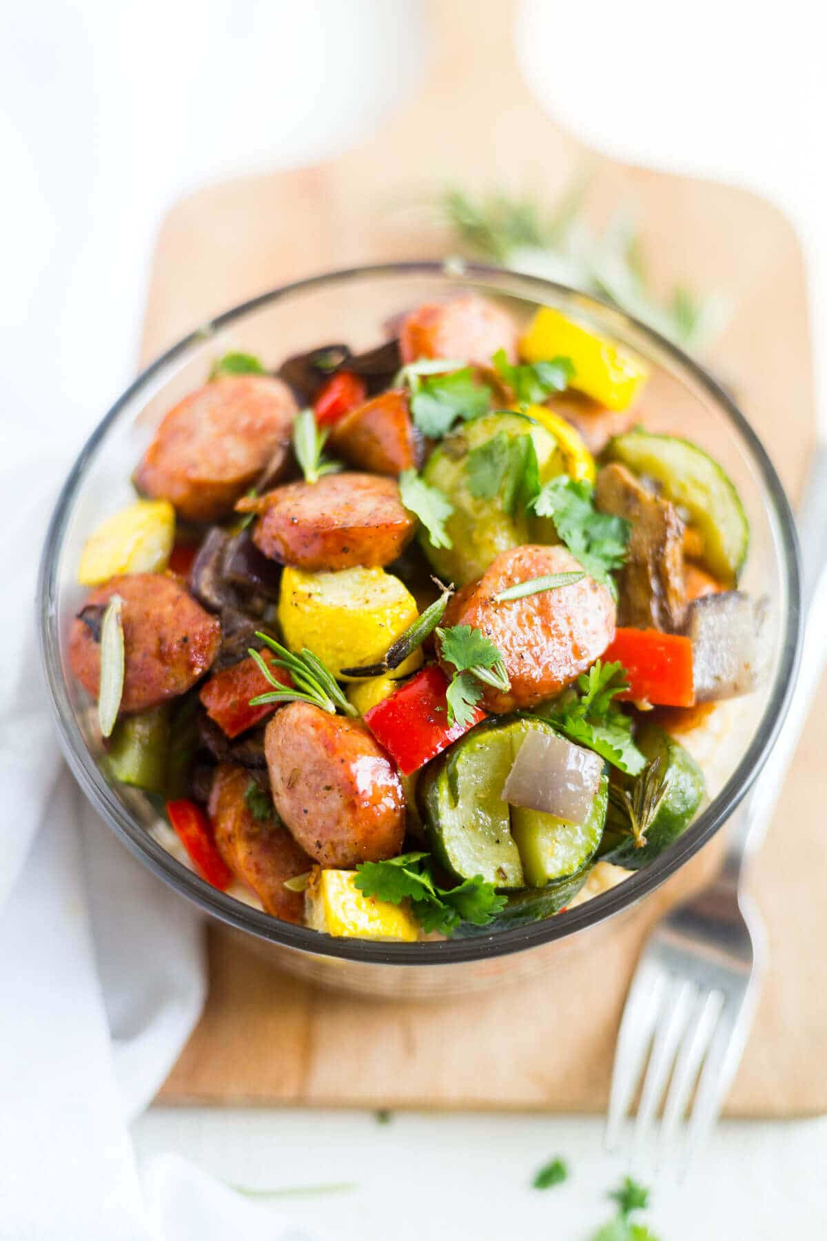 roasted sausage and veggies in a meal prep bowl topped with parsley