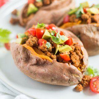 taco stuffed sweet potato on a plate with avocado