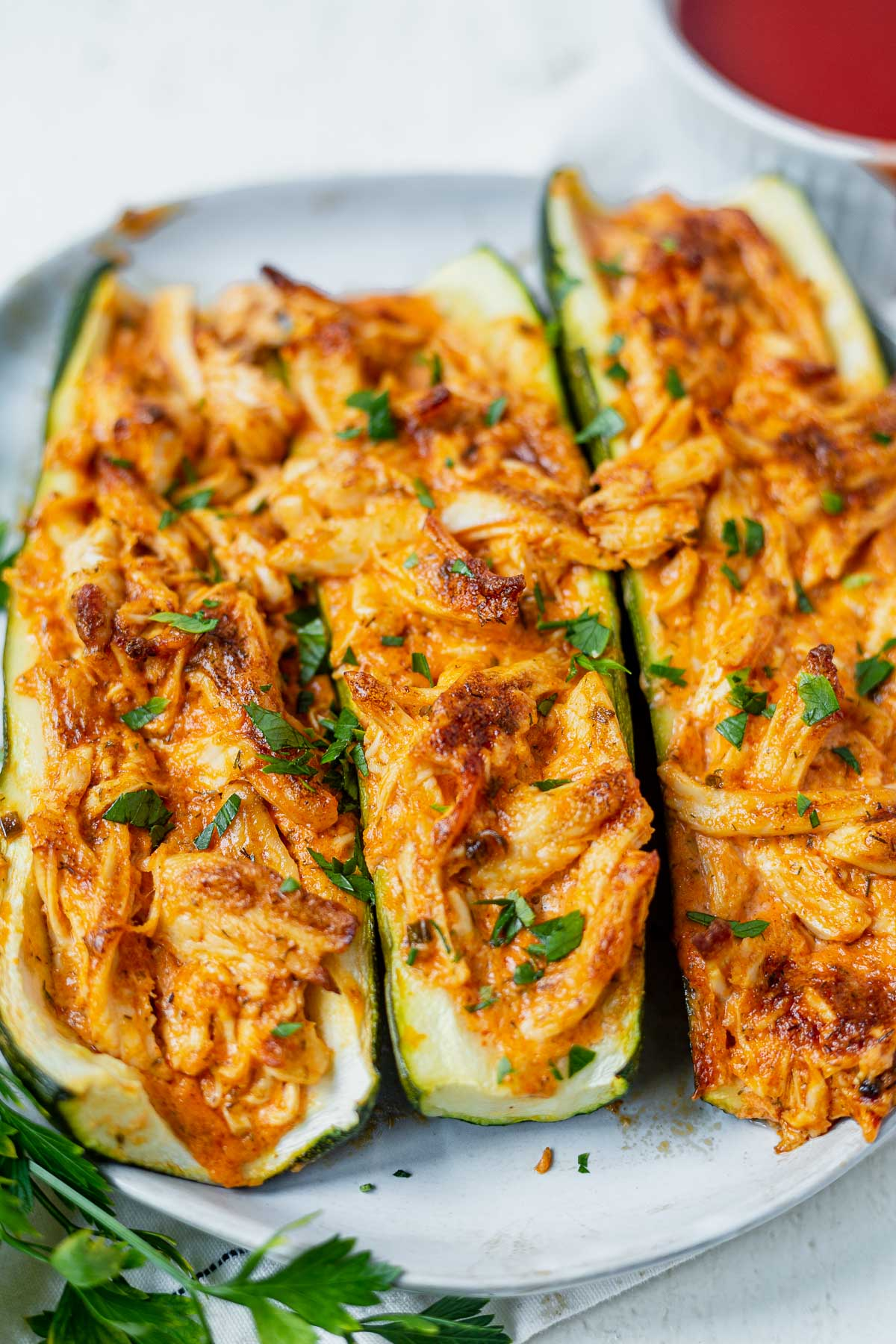 three buffalo chicken stuffed zucchini boats on a white plate topped with parsley