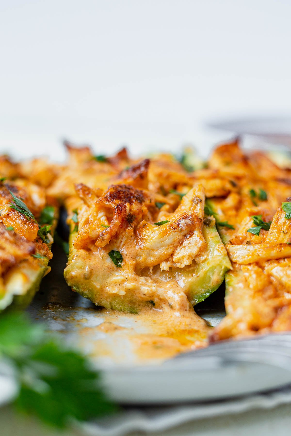 buffalo chickcen zucchini boats on a white plate with one cut in half