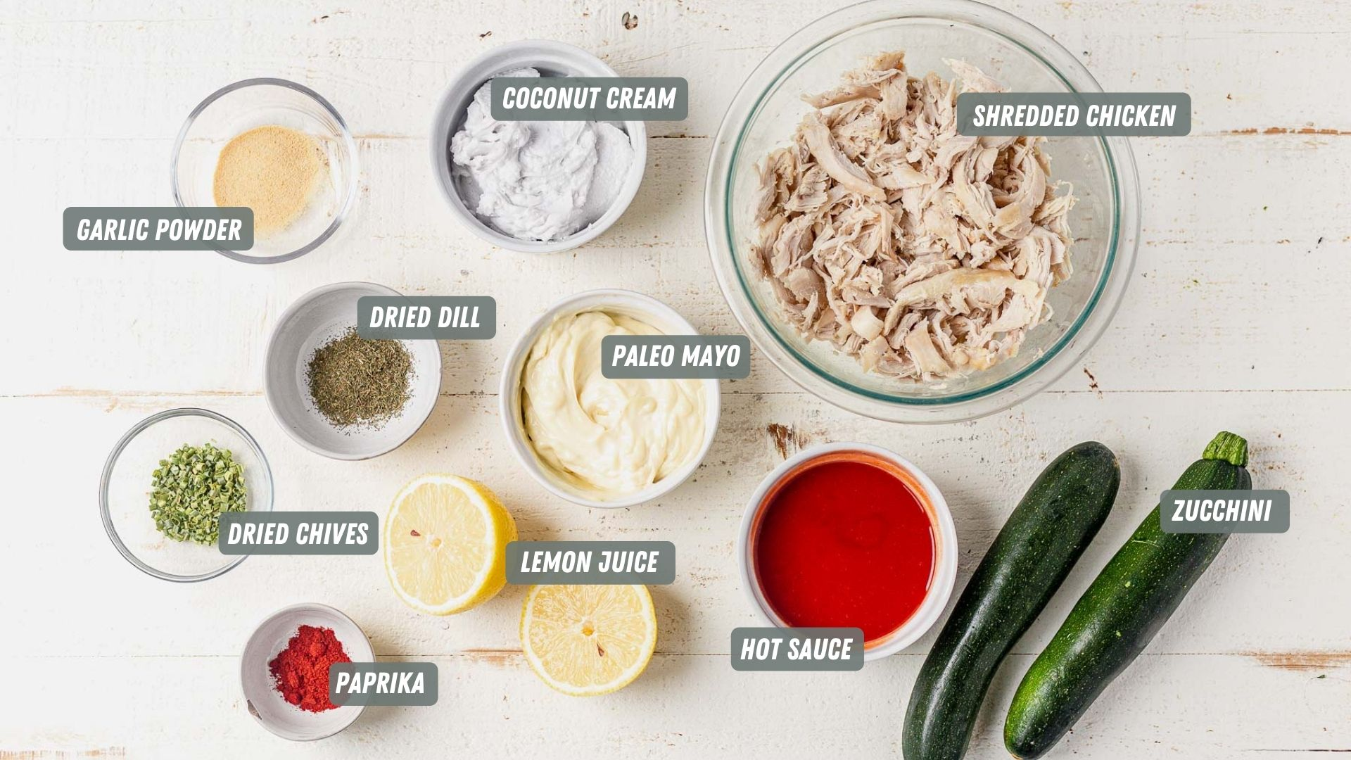ingredients for buffalo chicken zucchini boats on a white table