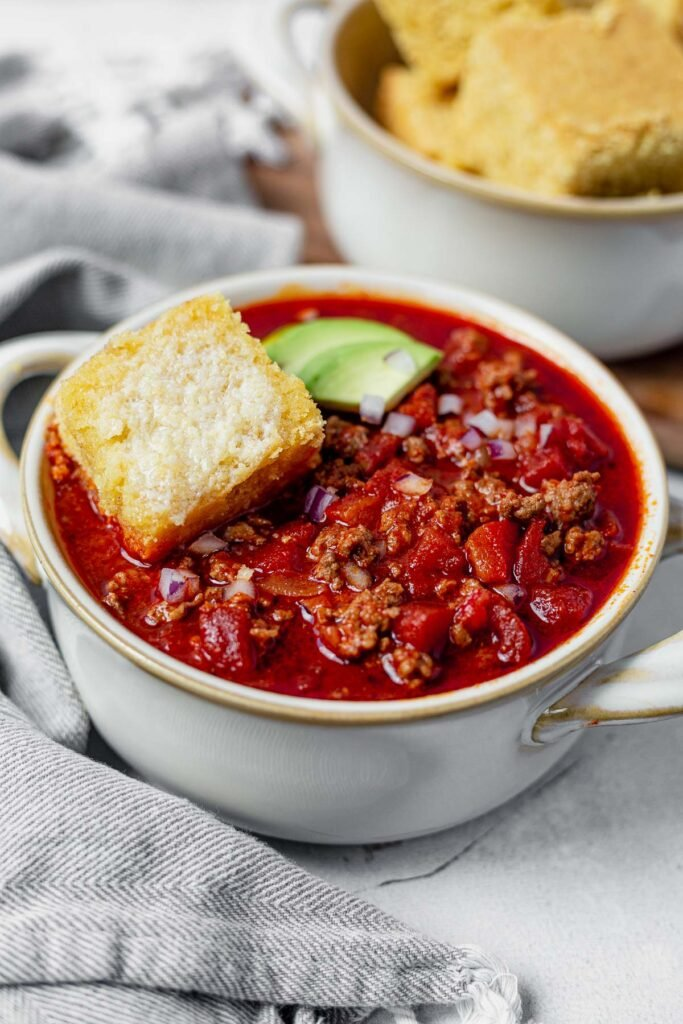 a big bowl of beanless chili with a slice of cornbread on top
