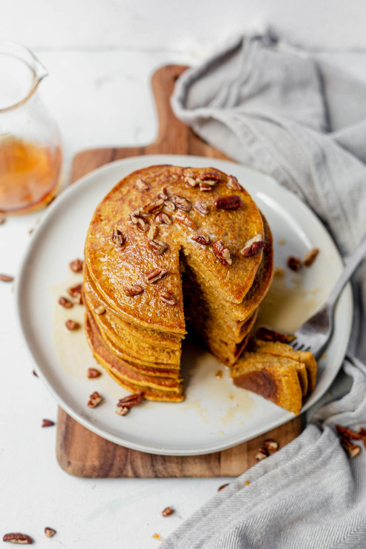 healthy pumpkin pancakes on a white plate topped with pecans and maple syrup