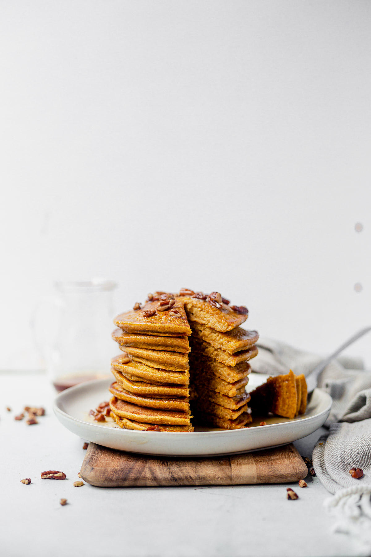a stack of healthy pumpkin pancakes with a triangle slice cut out of the side