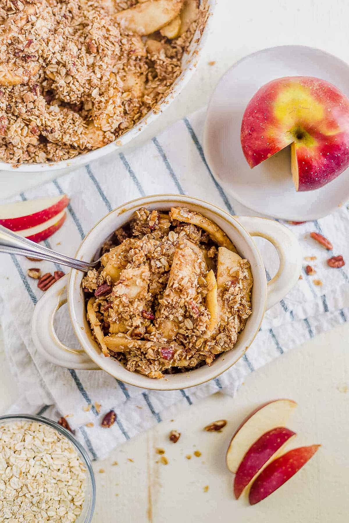 healthy apple crisp in a white bowl with sliced apples on the side