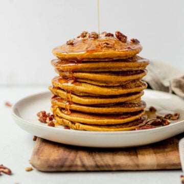 healthy pumpkin pancakes stacked on a white plate with syrup drizzling down the side