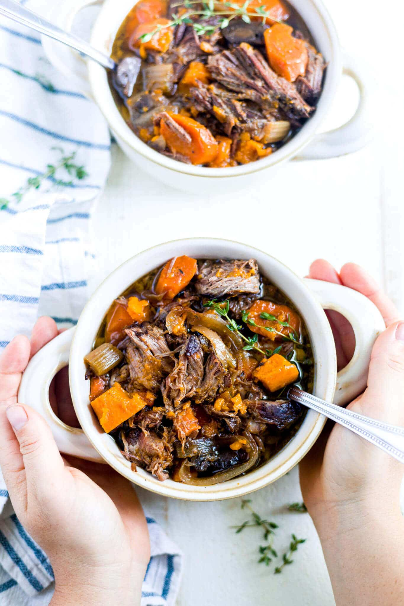 two hands holding a bowl of beef and sweet potato stew with a spoon