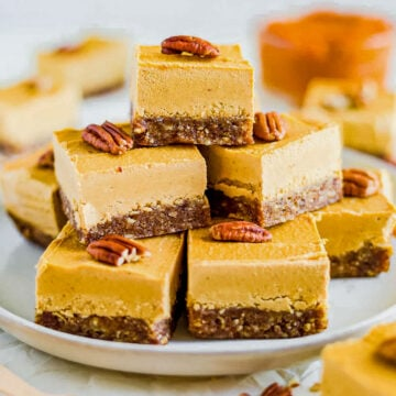 seven pieces of vegan pumpkin cheesecake arranged on a white plate