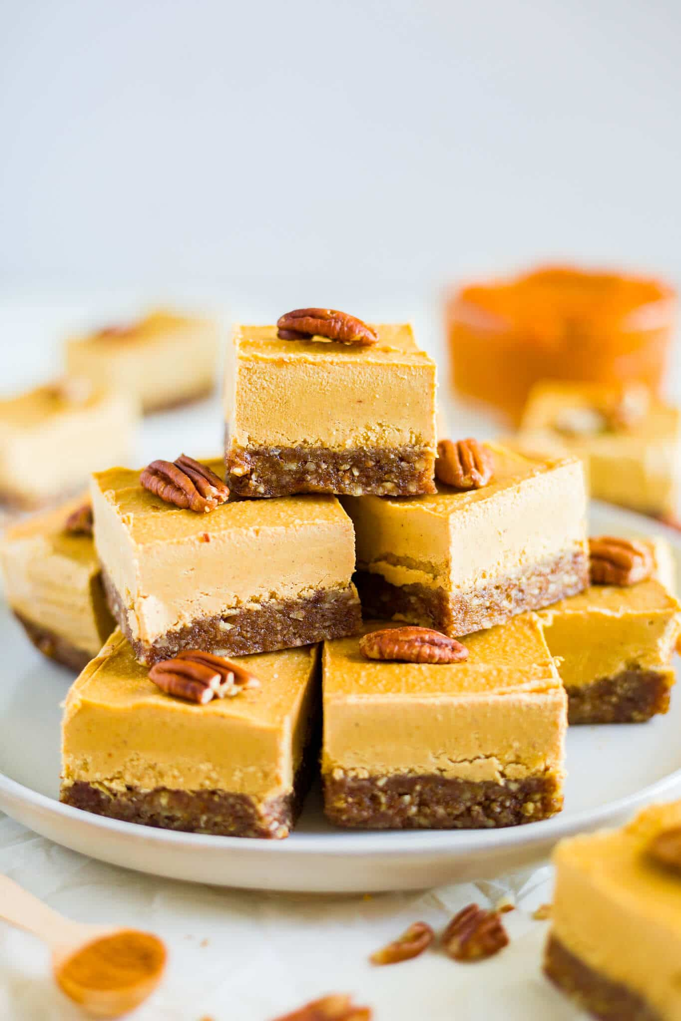 a stack of vegan pumpkin cheese on a white plate topped with pecans