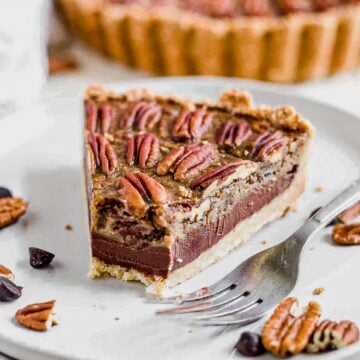a slice of chocolate paleo pecan pie surrounded by chocolate chips and pecans