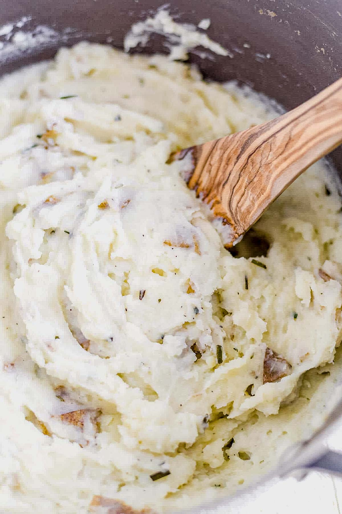 creamy dairy free mashed potatoes in a pot with a wooden spoon