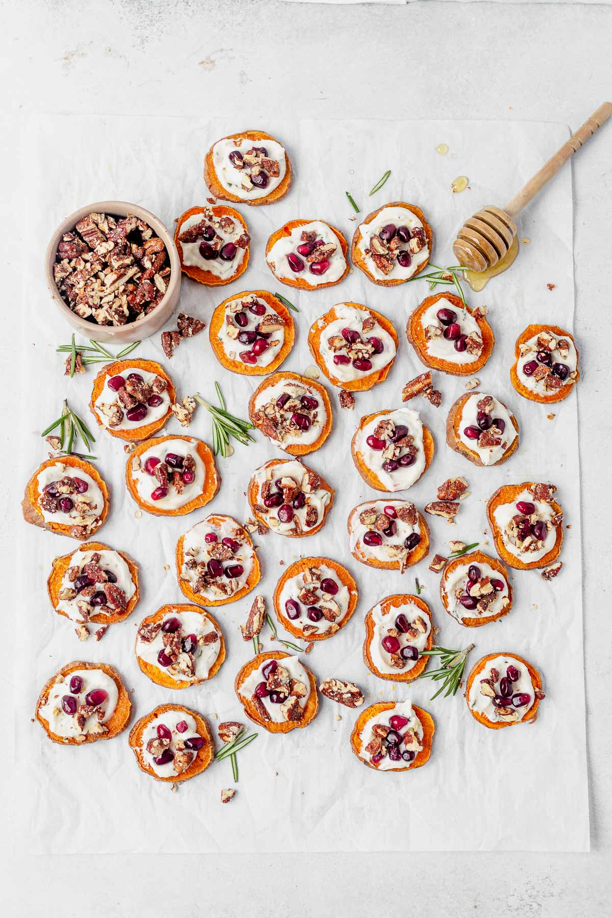 sweet potato bites displayed on white parchment paper with fresh honey and candied pecans
