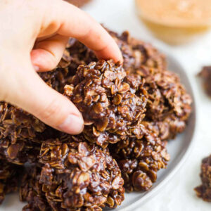 hand picking up a no bake chocolate oatmeal cookie off a plate of more cookies