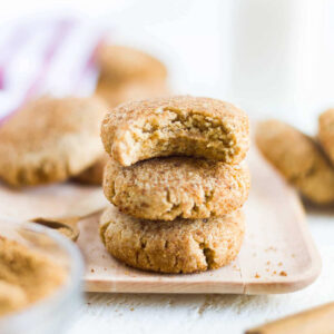 three paleo snickerdoodles sitting on a wooden plate with a bite taken out of the top one