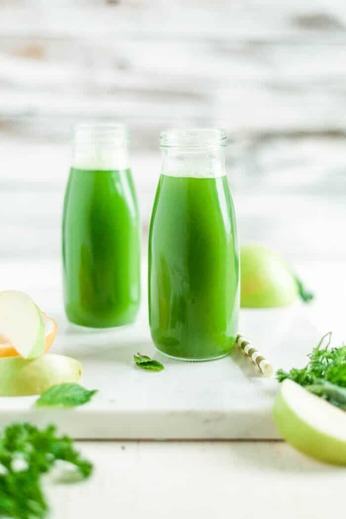 two glasses of green juice on a serving tray