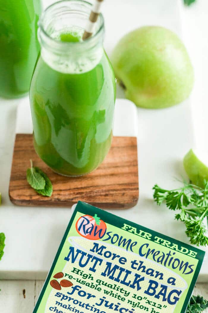 green juice in a glass jar on a wood coaster