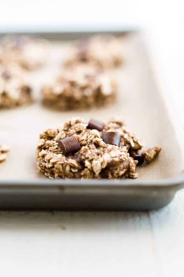 banana oatmeal chocolate chip cookies on a baking sheet with parchment paper