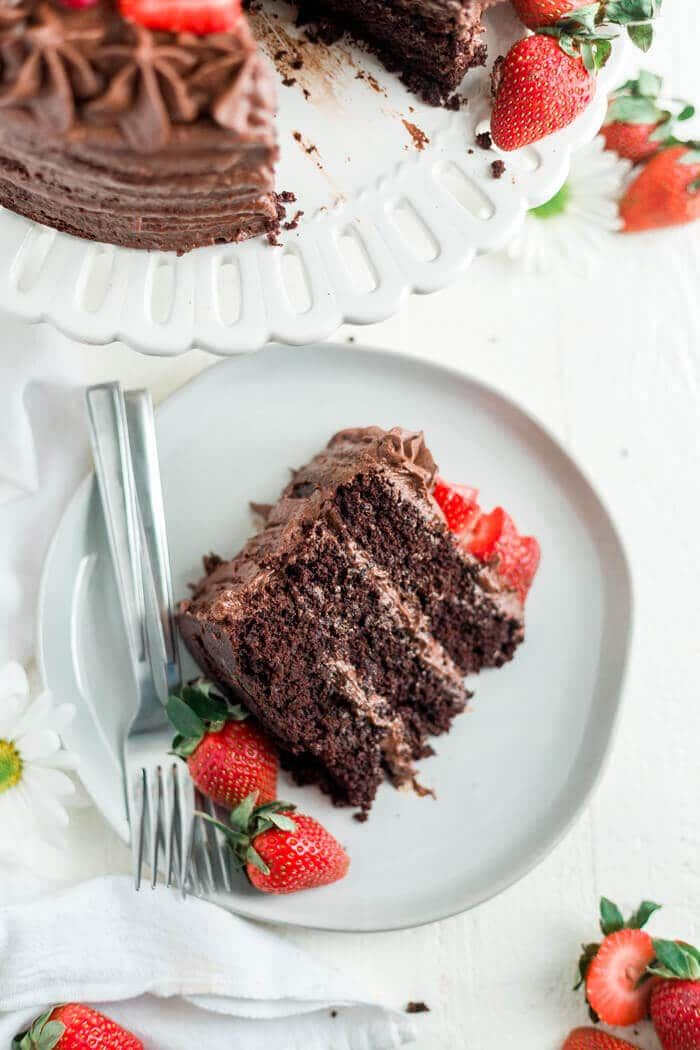 paleo chocolate cake recipe on a white plate with strawberries and two forks