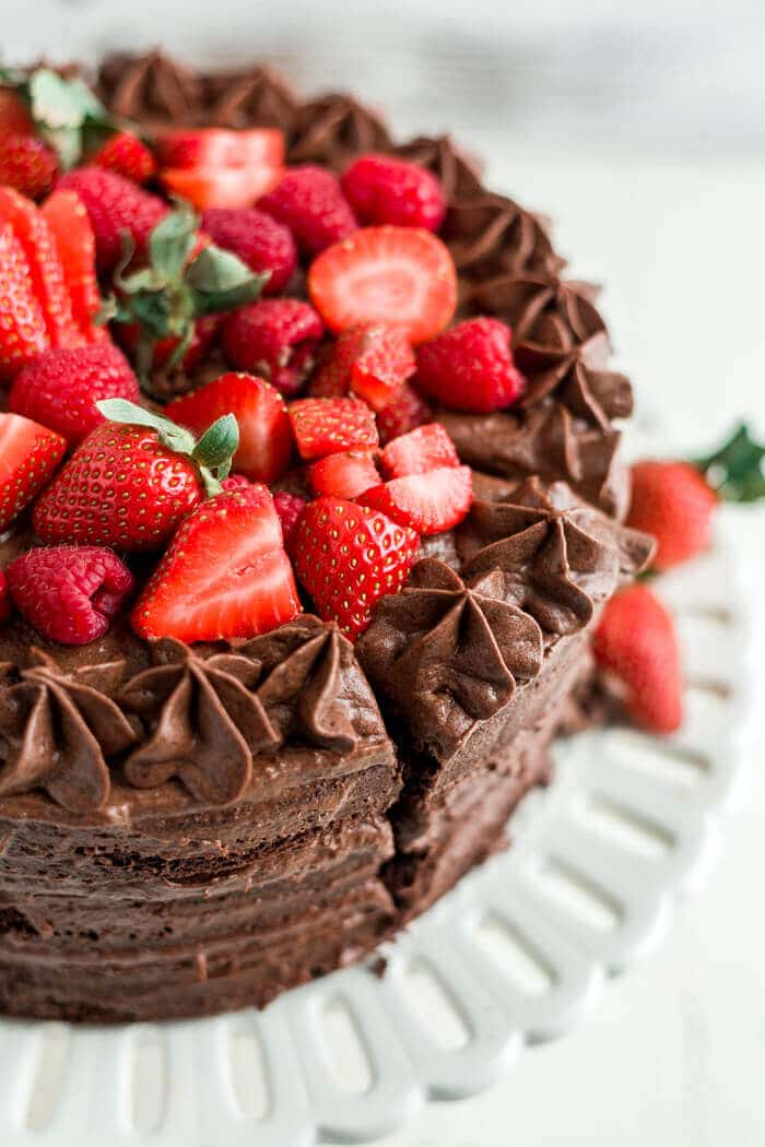 strawberries and raspberries on top of a paleo chocolate cake