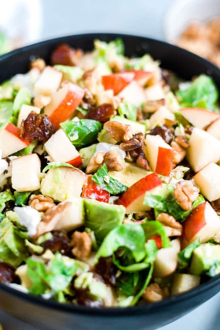 close up of apples, dates, avocado, goat cheese and walnuts in a shaved brussel sprout salad