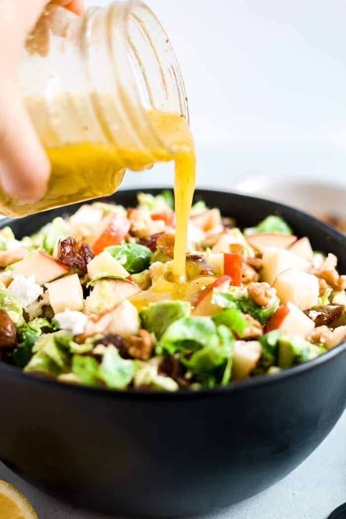 mustard vinaigrette being poured over shaved brussel sprout salad