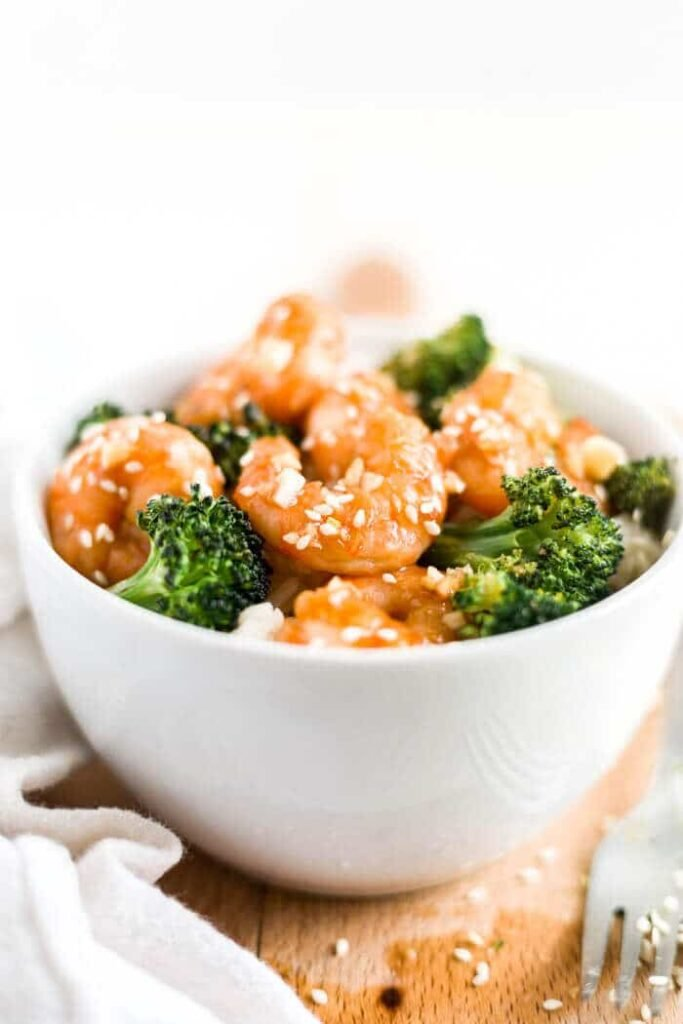 honey garlic shrimp in a bowl with rice and broccoli with a fork
