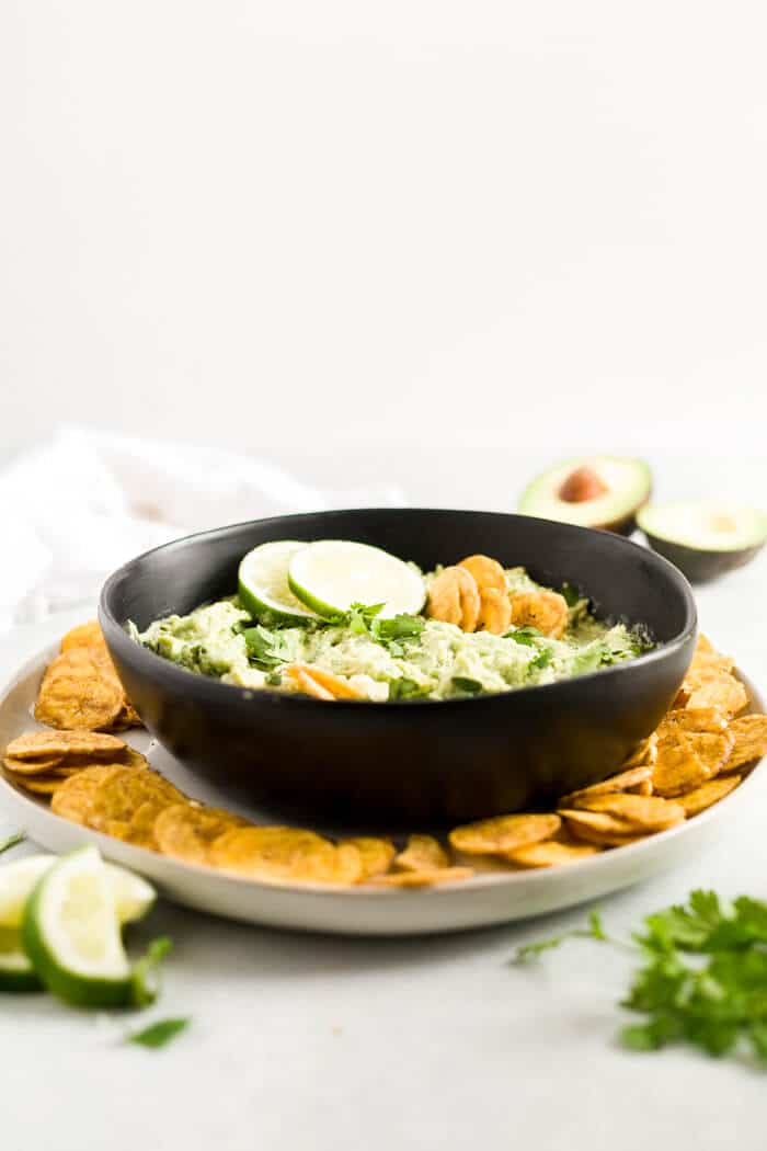 a plate of plantain chips with avocado dip and lime wedges