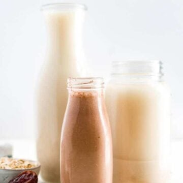 two glasses of homemade oat milk and one glass of chocolate oat milk