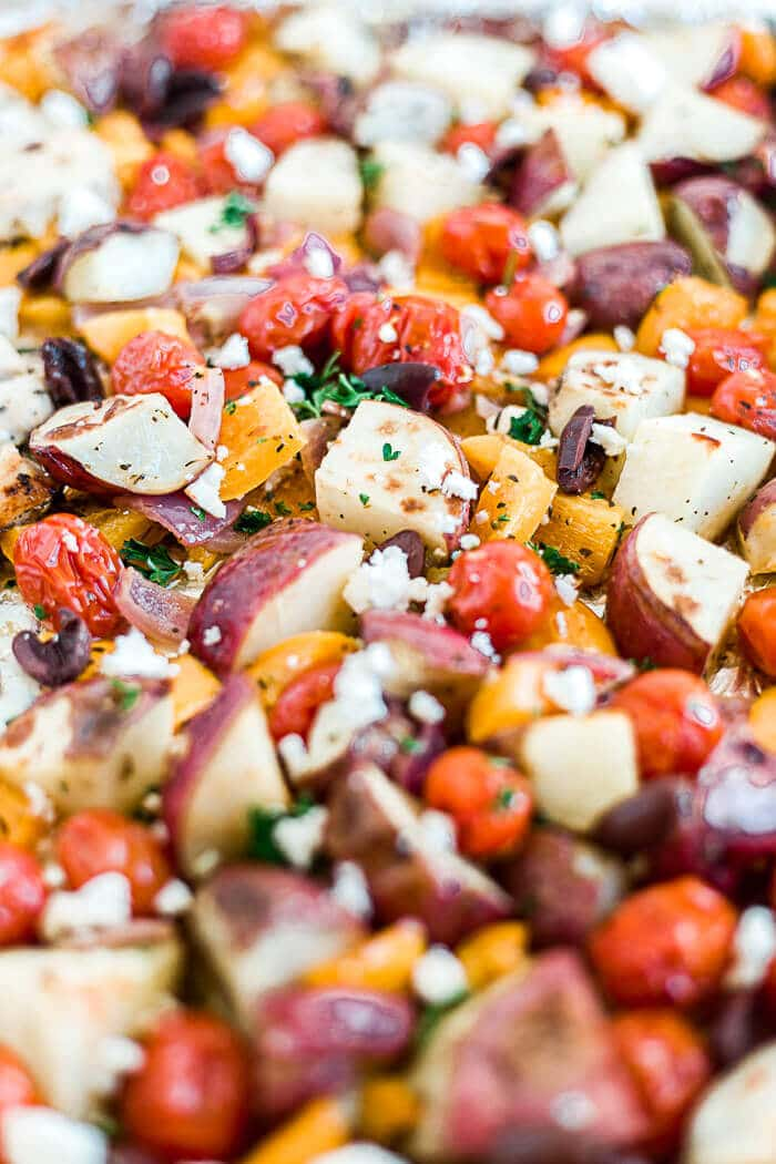 roasted red potatoes, tomatoes, peppers and onion with greek seasoning on a sheet pan