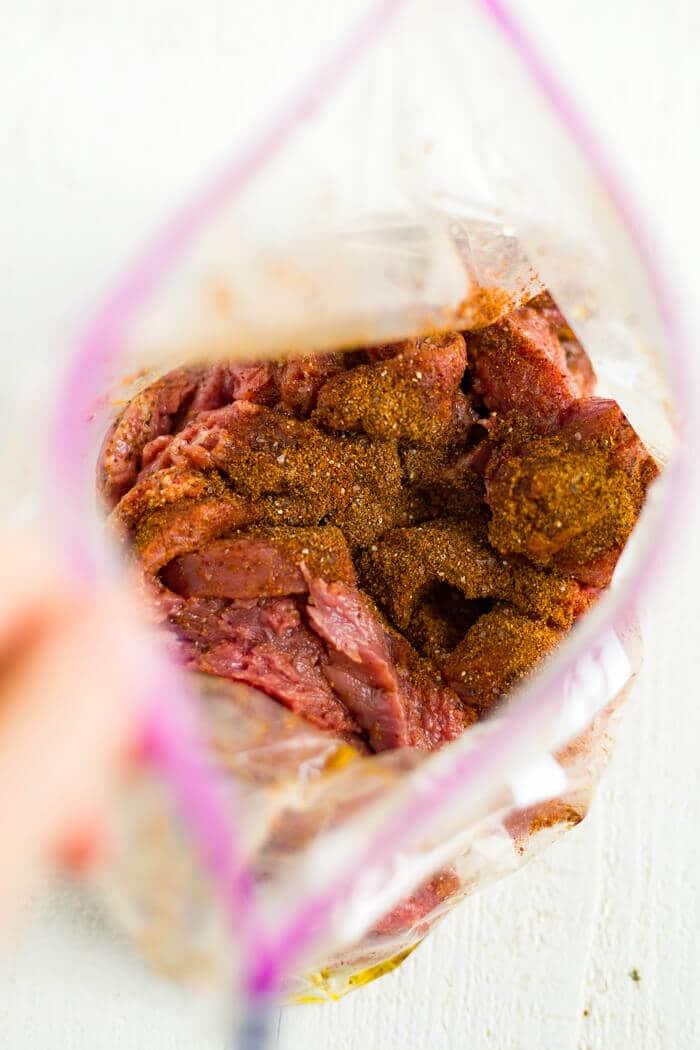 skirt steak with fajita seasoning in a plastic bag marinating for steak fajitas