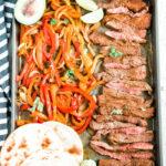 sheet pan steak fajitas on a tray with avocado, cilantro and toasted toritillas